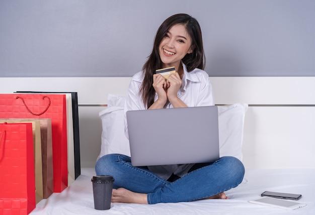 Heureuse femme utilisant un ordinateur portable pour faire du shopping en ligne avec carte de crédit sur le lit