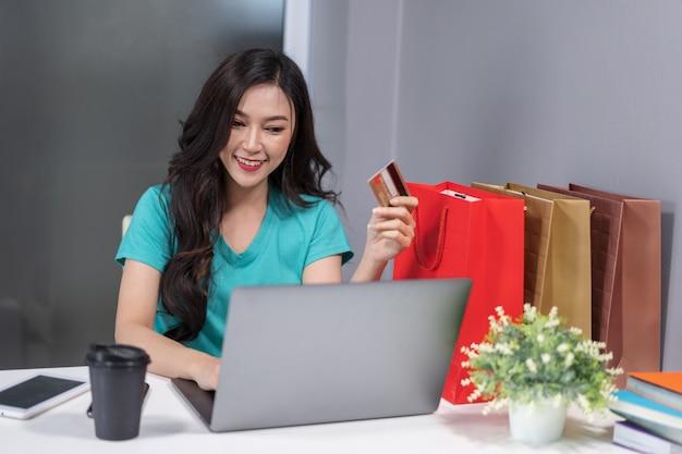 Heureuse femme utilisant un ordinateur portable pour faire du shopping en ligne avec carte de crédit
