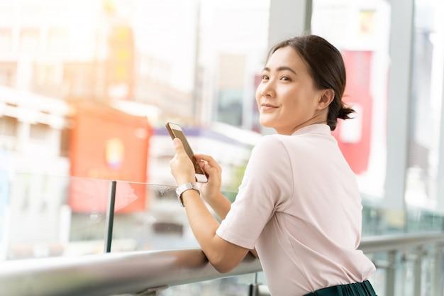 Heureuse femme utilisant un téléphone intelligent dans la ville