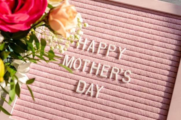 Heureuse fête des mères plat avec panneau de lettre rose et fleurs de printemps.