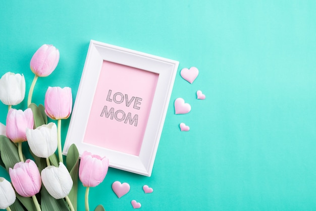 Heureuse fête des mères en vue de dessus de fleurs de tulipes roses et cadre photo
