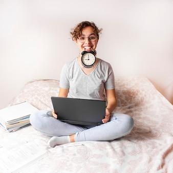 Heureuse fille adolescente drôle étudie sur le lit sur ordinateur et garde le réveil sur sa bouche