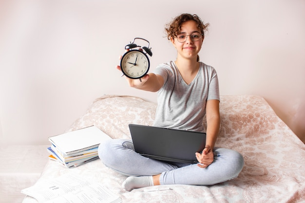 Heureuse fille adolescente drôle étudie sur le lit sur ordinateur et garde le réveil