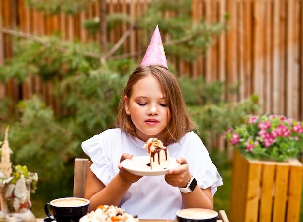 Heureuse fille adorable mangeant un gâteau d'anniversaire en terrasse de café. 10 ans fêtent l'anniversaire.