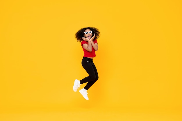 Heureuse fille afro-américaine à la mode sautant en l'air avec les mains sur le menton isolé sur mur jaune