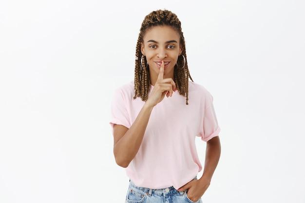 Heureuse fille afro-américaine souriante dire secret, geste chut, chut