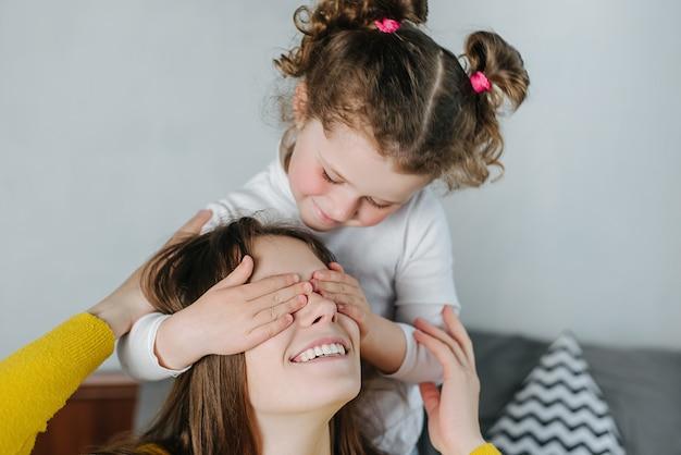 Heureuse fille d'âge préscolaire joyeuse faisant une surprise couvrant les yeux d'une maman souriante assise sur le lit à la maison. fin, haut, mignon, petite fille, amusez-vous, jouer, aimer, jeune, mère, passer, temps, ensemble