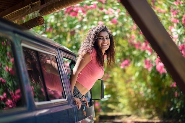 Heureuse fille arabe furtivement par la fenêtre d'une fourgonnette