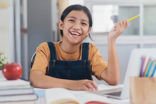 Heureuse fille asiatique, apprendre en ligne à la maison