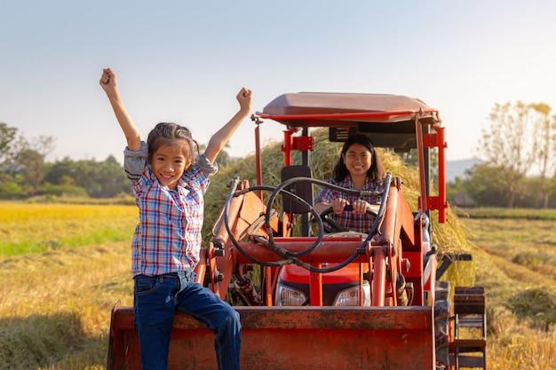 Heureuse fille asiatique assise à l'avant du tracteur avec sa mère conduisant un tracteur dans une rizière