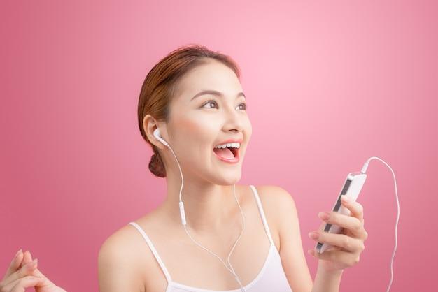 Heureuse fille asiatique dansant et écoutant de la musique isolée sur fond rose