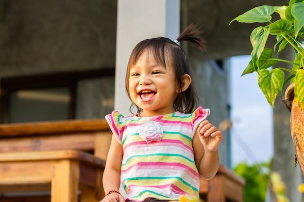 Heureuse fille asiatique enfant sourit et rit.