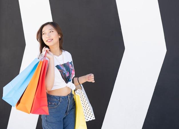 Heureuse fille asiatique, faire du shopping avec des sacs colorés