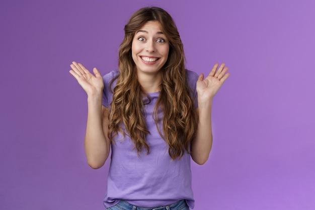 Heureuse fille aux cheveux bouclés enthousiaste et insouciante, haussant les épaules, écartant les mains sur le côté souriant insouciante indifférente aux autres problèmes indifférents n'ayant aucun problème à nier l'implication