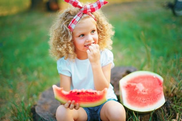 Heureuse fille bouclée assise sur une souche et manger de la pastèque à l'extérieur dans le parc du printemps