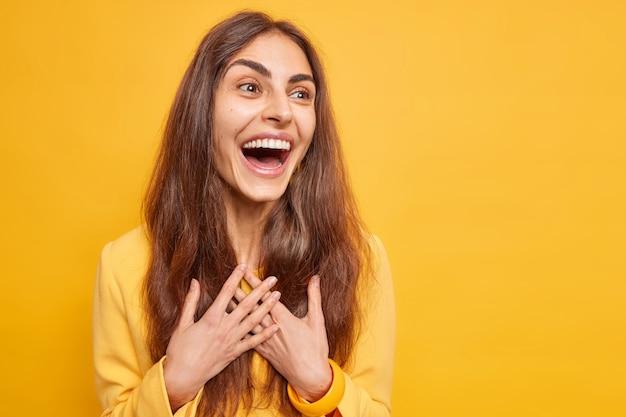 Heureuse fille brune candide sourit largement garde les mains sur la poitrine