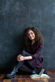 Heureuse fille brune frisée assise sur le sol