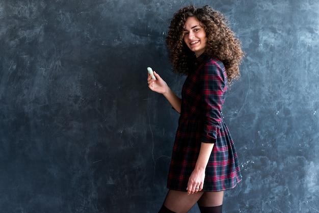 Heureuse fille brune frisée tient la craie dans sa main, debout près du tableau dans une robe à carreaux, étudiant
