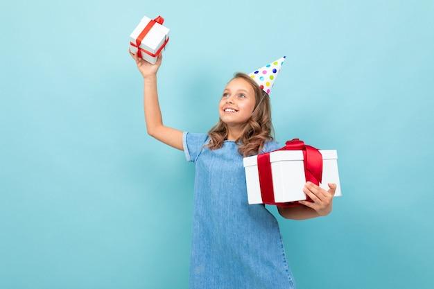 Heureuse fille caucasienne avec un chapeau de vacances tenant ses cadeaux bleu clair