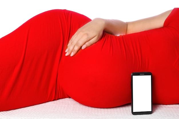 Heureuse fille enceinte attend un bébé avec une tablette se trouve sur un fond blanc. médecine pour les femmes message sur tablette.