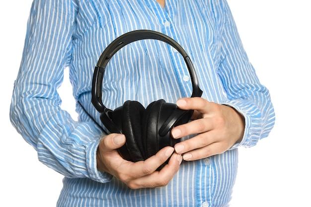 Heureuse fille enceinte avec un casque dans les mains dans les mains sur un mur blanc. musique positive pour l'enfant.