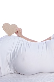 Heureuse fille enceinte se trouve sur le mur blanc