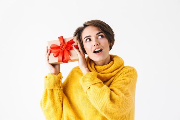 Heureuse fille gaie portant un chandail à capuchon debout isolé sur blanc, tenant une boîte-cadeau