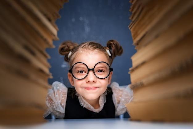 Heureuse fille intelligente dans des verres arrondis assis entre deux piles de livres et regarde la caméra en souriant.