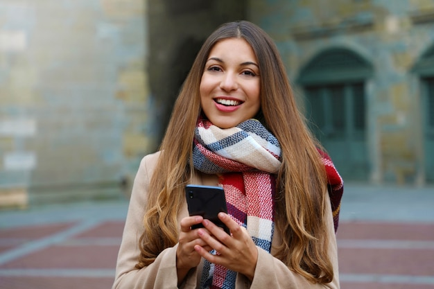 Heureuse fille joyeuse messagerie avec application de téléphone intelligent regardant ca