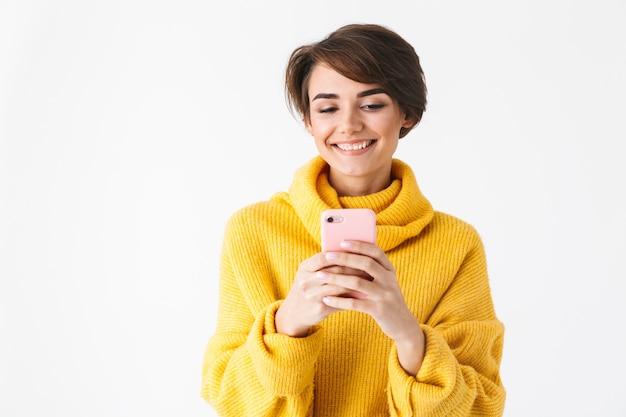 Heureuse fille joyeuse portant un sweat à capuche debout isolé sur blanc, à l'aide de téléphone mobile
