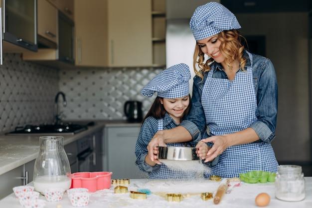 Heureuse fille et mère font remuer la pâte. concept de famille