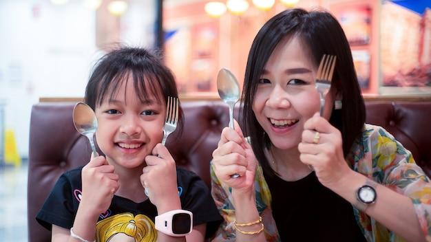 Heureuse fille et mère prête à manger la nourriture au restaurant. concept de fête des mères