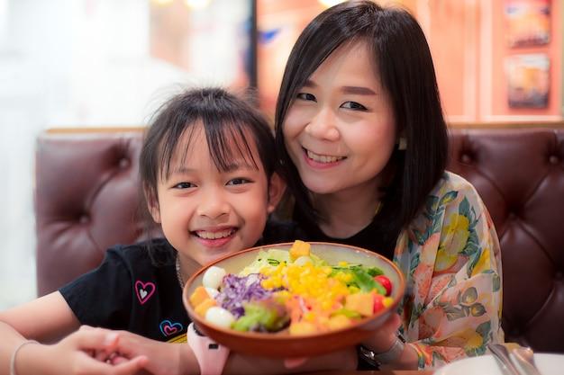 Heureuse fille et mère tenant une salade de légumes au restaurant. concept de fête des mères
