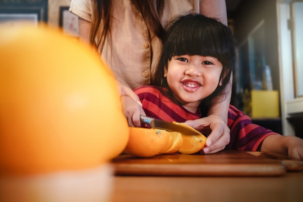 Heureuse fille mignonne de 3-4 ans avec sa mère tranche un peu d'orange sur une table en bois dans la salle pantry