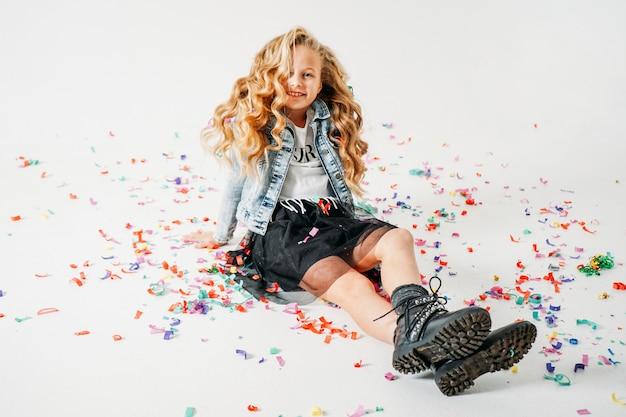Heureuse fille à la mode entre les cheveux bouclés tween girl dans une veste en jean et une jupe tutu noire et des bottes rugueuses assis sur blanc avec des confettis colorés