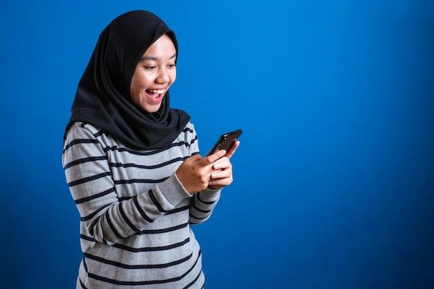Heureuse fille musulmane asiatique souriante en naviguant sur internet ou en lisant un message de discussion sur son téléphone