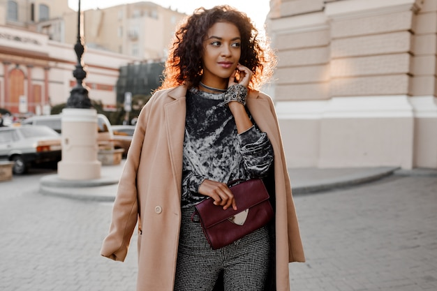 Heureuse fille noire avec un sourire candide dans un incroyable pull en velours gris, un manteau en laine beige, des accessoires de bijoux de luxe marchant à paris près du théâtre.