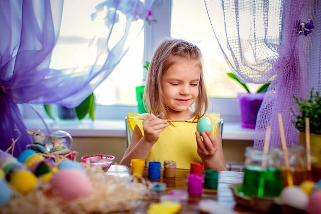 Heureuse fille peignant des oeufs de pâques, petit enfant à la maison s'amuser. vacances de printemps