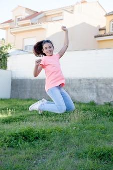 Heureuse fille preteen sauter à l'extérieur