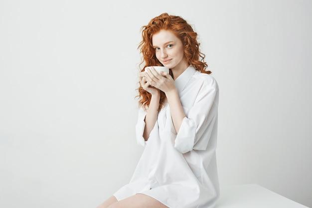 Heureuse fille rousse tendre en chemise souriant tenant la tasse assis sur la table