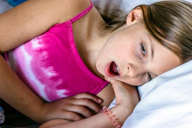 Heureuse fille se réveiller en étirant les bras sur le lit