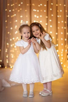 Heureuse fille soeur fond de lumières de noël bokeh d'or