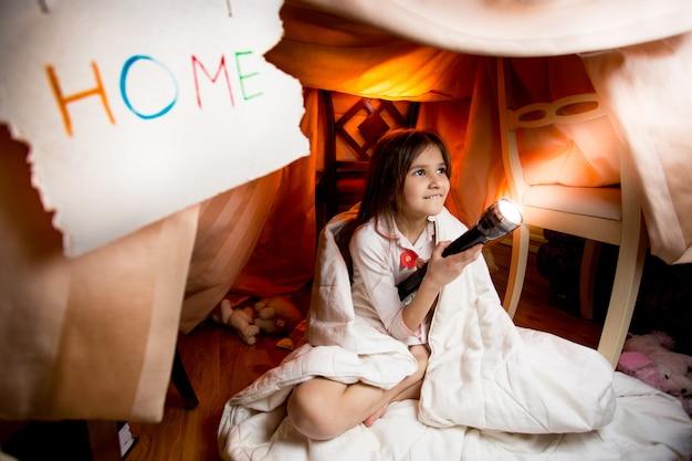 Heureuse fille souriante éclairant la chambre la nuit avec une lampe de poche