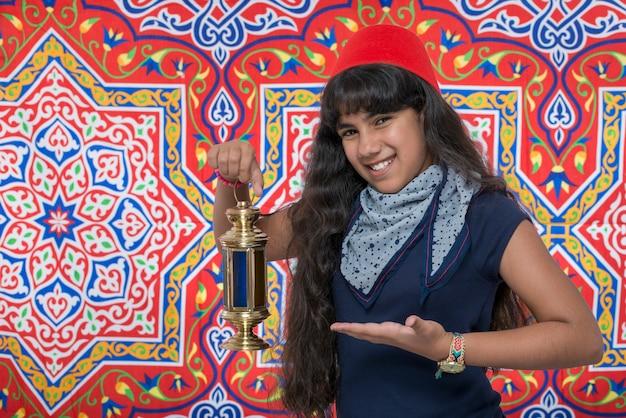 Heureuse fille souriante avec lanterne célébrant le ramadan