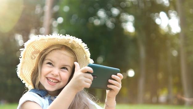 Heureuse fille souriante à la recherche de téléphone portable à l'extérieur en été.
