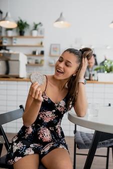 Heureuse fille souriante tient le cookie dans un café confortable.