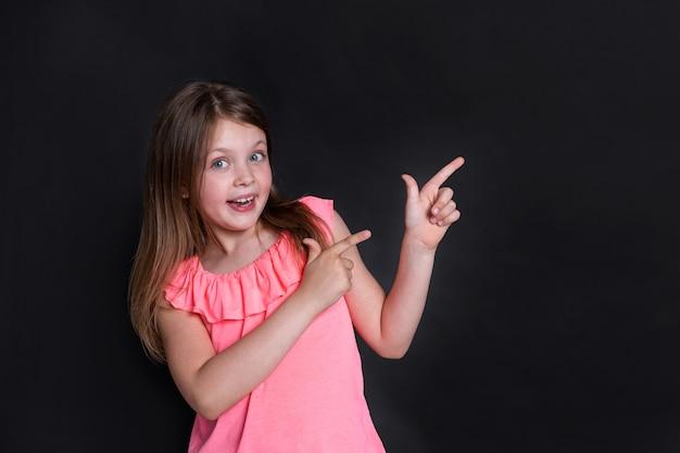 Une heureuse fille surprise pointe vers la droite avec ses mains avec ses doigts vers le haut