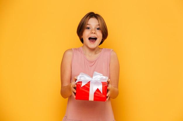 Heureuse fille surprise tenant un cadeau rouge isolé sur jaune