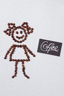 Heureuse fille symbolique faite de grains de café. surface isolée blanche.