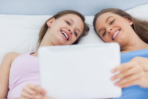 Heureuse filles couché dans son lit, tenant la tablette
